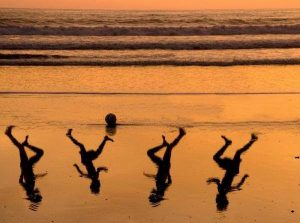 Children playing ball on the beach at sunset